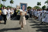 <p>A nun (C) holds a portrait of Cuban opponent leader Oswaldo Paya during his burial on July 24 at Cristobal Colon Cemetery in Havana. Paya's widow has rejected a government report that blamed the car crash that killed her husband on the driver, saying she had been denied access to information.</p>