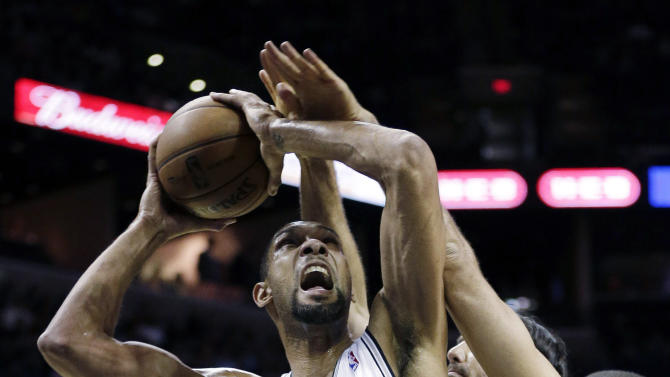 San Antonio Spurs' Tim Duncan (21) is fouled by Phoenix Suns' Luis Scola, rear, of Argentina, during the first half of an NBA basketball game, Wednesday, Feb. 27, 2013, in San Antonio. Suns' Wesley Johnson, right, also defends on the play. (AP Photo/Eric Gay)