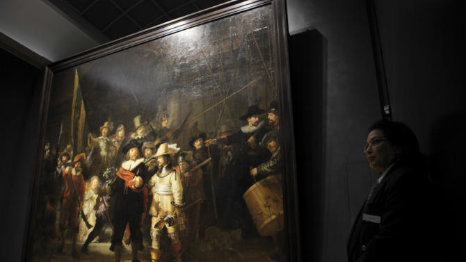 """EXPANDS ORIGINAL CAPTION -- security guard stands next to Rembrandt's """"Night Watch"""" painting, illumintaed by newly installed LED lights in Amsterdam, Netherlands, Wednesday Oct. 26, 2011. The """"Night Watch"""" may need a different nickname after the painting has been put under new lighting that makes it look like a day scene. The change is startling, as characters once barely visible now stand out in vivid color.  The 1642 painting was commissioned for one of Amsterdam's citizen militias and is officially titled """"The Company of Frans Banning Cocq."""" Director Wim Pijbes of the national Rijksmuseum said Wednesday the painting , widely considered Rembrandt's greatest masterpiece, may in fact only have acquired the """"Night Watch"""" name due to a dark varnish that was removed decades ago. He said the new LED lighting system custom designed by Philips mimicks daylight, helping return the work to its original dynamic, colorful appearance.  (AP Photo/Peter Dejong)"""