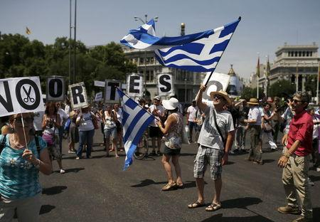 A man waves a Greek national flag during a rally in support of Greece, in Madrid