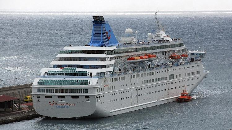 The British-operated cruise ship Thomson Majesty is seen docked in the port of Santa Cruz on the Canary Island of La Palma, Spain, Sunday Feb. 10, 2013, with orange rescue boat, below right, seen docked next to a capsized lifeboat. A lifeboat from the Thomson Majesty fell into the sea at port in Spain's Canary Islands, killing five people and injuring three others Sunday, officials said. Rescue personnel were called to the dockside after a lifeboat with occupants had fallen overboard from a cruise ship. Spanish national broadcaster RTVE said an emergency training drill was taking place at the time of the accident. (AP Photo/Manuel Gonzalez)
