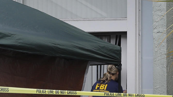 An FBI investigator enters the apartment  where a man was shot by an FBI agent, Wednesday, May 22, 2013, in Orlando, Fla. The FBI says the man, being questioned by authorities in the Boston bombing probe, was fatally shot when he initiated a violent confrontation. (AP Photo/John Raoux)