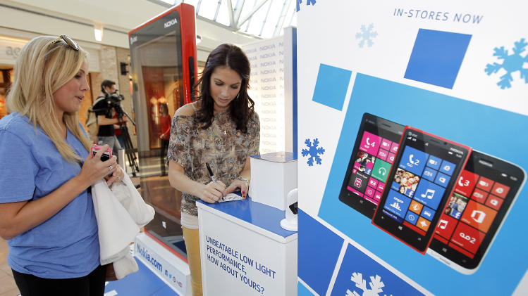 Melissa Rycroft, right, autographs a piece of paper for Ashlan Dubose at the Nokia Experience on Tuesday, Dec. 18, 2012 in Frisco, Texas. (Photo by Brandon Wade/Invision for Nokia/AP Images)