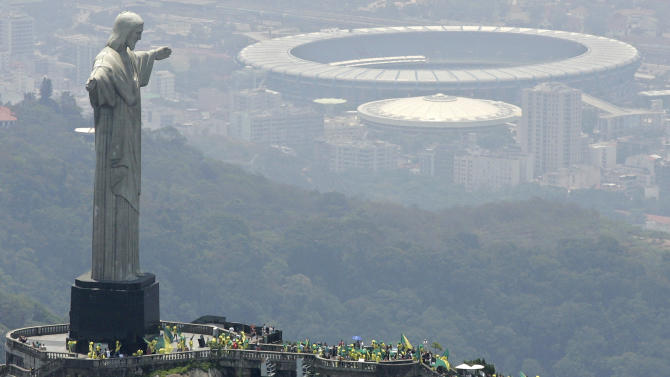 """FILE - In this Oct. 30, 2007 file photo, people wave flags at the top of Corcovado mountain, in front of the statue, Christ the Redeemer, in Rio de Janeiro, after Brazil was officially chosen by FIFA as the host country for the 2014 World Cup. Brazil's foreign minister says """"all necessary measures"""" are being taken to ensure security at next year's soccer World Cup and the 2016 Olympics following the deadly explosions at the Boston Marathon. While Brazil has never been a target of international terrorism, Monday's attacks underscore how vulnerable big sporting events can be. Rio will also host two major events later this year, the Confederations Cup soccer tournament and the World Youth Day, a Roman Catholic pilgrimage that's expected to be attended by Pope Francis and as many as 2.5 million visitors. (AP Photo/Andre Penner, File)"""