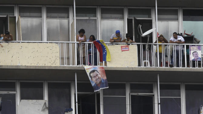 Supporters of Venezuela's acting President Nicolas Maduro hold posters of late President Hugo Chavez from a building overlooking the national electoral council as Maduro registers his presidential candidacy to replace Chavez in Caracas, Venezuela, Monday, March 11, 2013. Presidential elections were announced to take place on April 14, after Maduro announced the death of Chavez on March 5. (AP Photo/Fernando Llano)