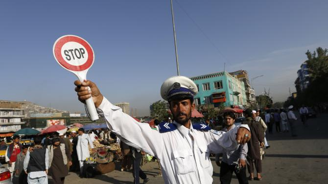 An Afghan traffic policeman directs vehicles on a busy road in Kabul