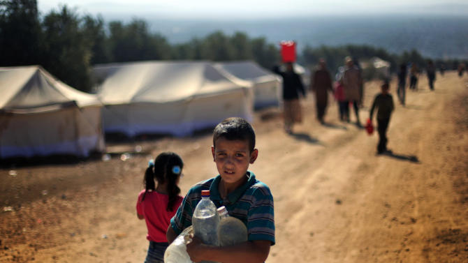 A Syrian boy who fled with his family from the violence in their village, carries water bottles at a displaced camp, in the Syrian village of Atma, near the Turkish border with Syria, Monday, Nov. 5, 2012. (AP Photo/ Khalil Hamra)