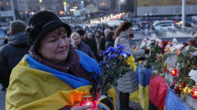 Woman reacts as she visits the site where anti-Yanukovich protesters were killed during clashes in Kiev