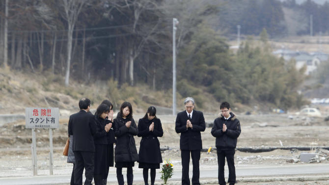 Kumi Kotsuji, second from left, who lost her parents and sister in the March 11, 2011 earthquake and tsunami prays with relatives at the site where her family's house once stood, in Rikuzentakata, Iwate prefecture, northeastern Japan, Sunday, March 11 2012. Japan on Sunday was remembering the massive earthquake and tsunami that struck the nation one year ago, killing just over 19,000 people and unleashing the world's worst nuclear crisis in a quarter century.  (AP Photo/Koji Sasahara)