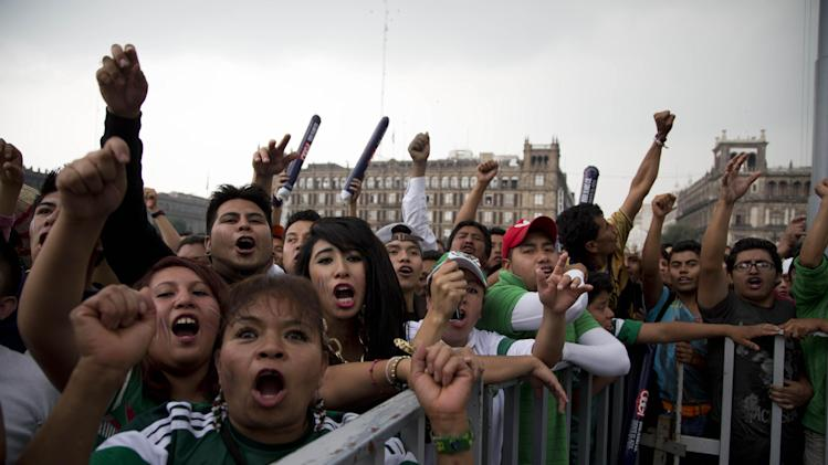 Mexico fans cheer as they watch their team's 2014 World Cup match with Croatia on giant television screens in Mexico City's main square, the Zocalo, Monday, June 23, 2014. Needing only a tie to advance to the second round of the World Cup for a sixth straight time, Mexico is bound to please its fans