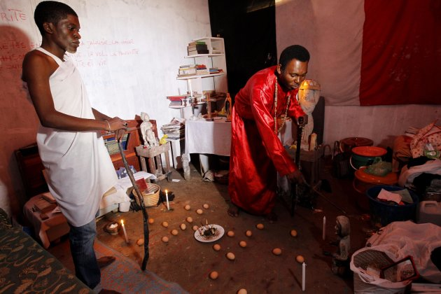Spiritual mediums Azaelis and Nziengui prepare a mock soccer stadium with mystical effigies inside their shrine in Libreville