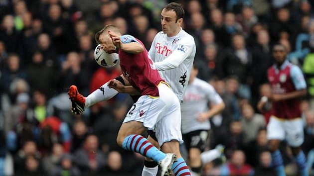 Aston Villa's Nathan Baker (left) clashes with Fulham's Dimitar Berbatov (right)