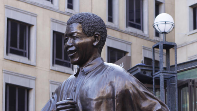 Visitors to Nelson Mandela Square in Johannesburg beneath a giant statue of the former president Monday, April 1, 2013. The presidential spokesman says former president Mandela spent Monday with family members in the hospital where he is being treated for a fifth day for a recurring lung infection that developed into pneumonia. The 94-year-old who helped free South Africa from white minority rule has had weak lungs ever since he quarried stone on Robben Island during some of his 27 years of imprisonment. He contracted tuberculosis there. (AP Photo/Denis Farrell)