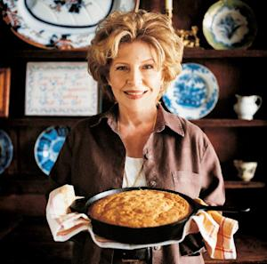 """FILE - In this undated photo provided by Viking, Jan Karon, author of the Mitford books, poses with a pan of cornbread, in this photo from """"Jan Karon's Mitford Cookbook & Kitchen Reader,"""" her new book about the little Southern town where the kitchen is """"the heart of the home."""" Nearly a decade after the novelist announced she was done with her multimillion-selling Mitford Years series, she has signed up with G.P. Putnam's Sons for two more installments about the fictional North Carolina town and such residents as Father Tim Kavanaugh and his wife, Cynthia. The next release, """"Somewhere Safe With Somebody Good,"""" is scheduled for September 2014. (AP Photo/Viking, Christopher Hirscheimer, File)"""