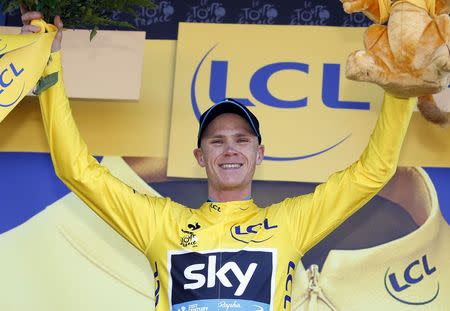 Team Sky rider Froome of Britain celebrates as he wears the race leader's yellow jersey on the podium of the third stage of the 102nd Tour de France cycling race