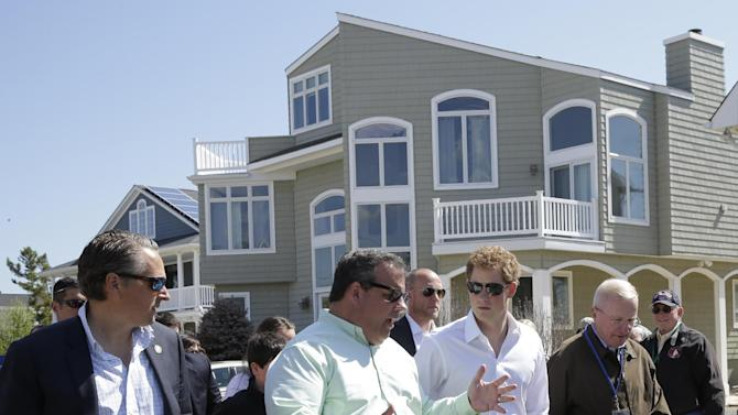 New Jersey Gov. Chris Christie, center left, walks with Britain's Prince Harry, center, while visiting the area hit by Superstorm Sandy, Tuesday, May 14, 2013, in Seaside Heights, N.J. New Jersey sustained about $37 billion worth of damage from the storm. (AP Photo/Mel Evans, Pool)