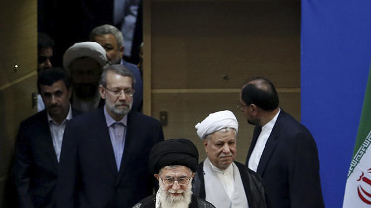 In this photo taken on Thursday, Aug. 30, 2012, and released by an official website of the Iranian supreme leader's office, supreme leader Ayatollah Ali Khamenei, center, and chief of Expediency Council, Akbar Hashemi Rafsanjani, second right, arrive at the opening session of the Nonaligned Movement, NAM, summit, in Tehran, Iran. Parliament speaker Ali Larijani, second left, and President Mahmoud Ahmadinejad, left, make their way. (AP Photo/Office of the Supreme Leader)