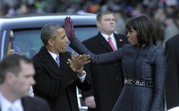 President Barack Obama and first lady Michelle Obama walk in the Inaugural Parade after the ceremonial swearing-in for the 57th Presidential Inauguration on Capitol Hill in Washington, Monday, Jan. 21, 2013. (AP Photo/Susan Walsh)