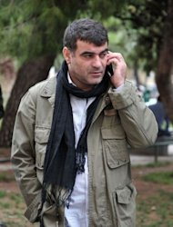 "Costas Vaxevanis, a 46-year-old veteran investigative journalist, speaks on the phone at a court in Athens. Several media workers had testified on behalf of Vaxevanis, including the head of the International Federation of Journalists, Jim Bumelha, who called the trial an ""absurd farce"""