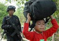 Indonesian police guard a Shiite Muslim boy as he is escorted to safety following attacks in Sampang on August 27. A mob attack on Shiites in Indonesia saw two men killed with sickles and dozens of homes torched, police and a human rights group said Monday, in the latest sign of rising intolerance in the world&#39;s largest Muslim country