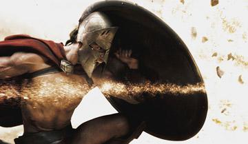 Stelios ( Michael Fassbender ) crouches behind his shield as shrapnel tears through the air in Warner Bros. Pictures' 300