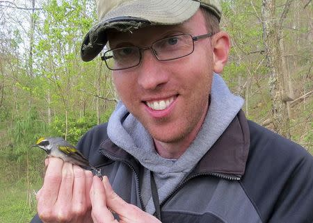 Henry Streby holds a male golden-winged warbler and the geolocator that the bird carried in the Cumberland Mountains of Tennessee