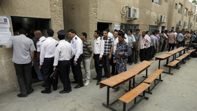 Iraqi security forces queue to vote at a polling center during the early voting in Baghdad, Iraq, Saturday, April 13, 2013. Voters head to the polls next week for the first time since the U.S. military withdrawal, marking a key test for Prime Minister Nouri al-Maliki's political bloc and for the security forces under his command that are charged with keeping voters safe. (AP Photo/ Khalid Mohammed)