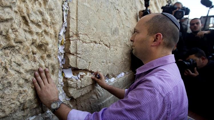 "FILE - In this Jan. 21, 2013 file photo, Naftali Bennett, head of the Jewish Home party, touches the stones of the Western Wall, the holiest site where Jews can pray, in Jerusalem's Old City. The idea of Palestinians establishing a state in the territory they seek has ""reached a dead end,"" Naftali Bennett, economics minister, said Monday, June 17, 2013, in the latest remarks by hard-liners that appear to contradict the country's official support for a ""two-state solution"" to its conflict with the Palestinians. (AP Photo/Sebastian Scheiner, File)"