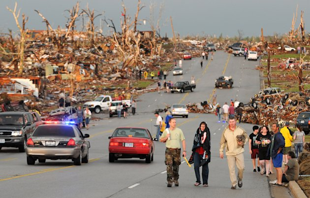 FILE - In this May 22, 2011 file photo, residents of Joplin, Mo., walk west on 26th Street near Maiden Lane after a tornado hit the southwest Missouri city. Some federal money pledged to tornado-ravag