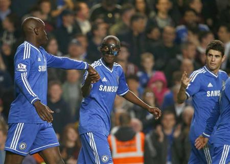 Chelsea's Demba Ba (L) celebrates with team mates Ramires (C) and Oscar after scoring a second goal against Tottenham Hotspur during their English Premier League soccer match at Stamford Bridge in