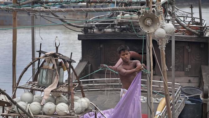 A Bangladeshi fisherman brings down his fishing net in a boat anchored on the banks of the river Kornofuli, in Chittagong, Bangladesh, Wednesday, May 15, 2013. Cyclone Mahasen is expected to make landfall early Friday. The storm was heading toward Chittagong, Bangladesh, but could shift east and deliver a more direct hit on Rakhine state in Myanmar. (AP Photo/A.M.Ahad)