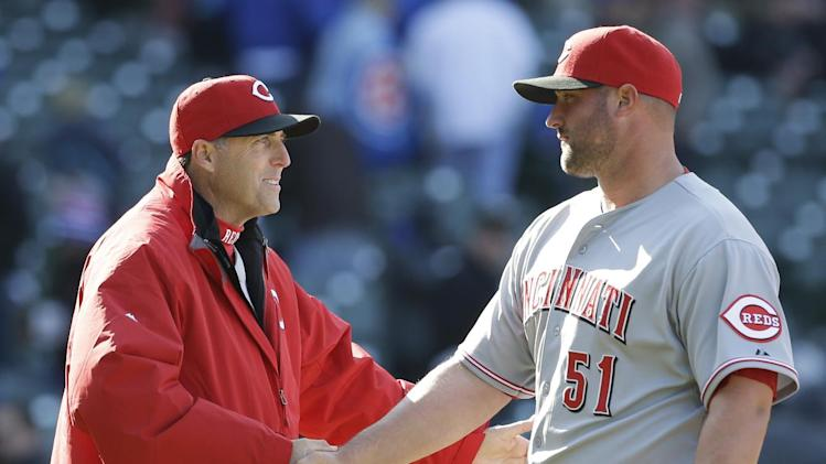 Cincinnati Reds manager Bryan Price, left, celebrates with closer Jonathan Broxton after they defeated the Chicago Cubs 4-1 in a baseball game in Chicago, Friday, April  18, 2014