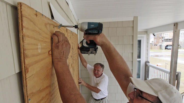 Residents Bill Novak, center, and Bill Jones board up windows in anticipation of the arrival of Hurricane Irene in Kill Devil Hills, N.C., Thursday, Aug. 25, 2011 on North Carolina's Outer Banks. (AP Photo/Charles Dharapak)