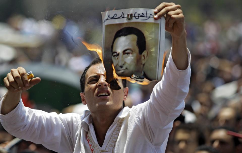 A man burns a picture of ousted Egyptian president Hosni Mubarak during a rally after Friday prayers in Tahrir Square, Cairo,  Friday, July 1, 2011.  (AP Photo/Sergey Ponomarev)