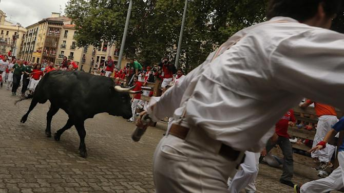 "Revelers run in front of a Victoriano del Rio ranch fighting bull during the running of the bulls of the San Fermin festival, in Pamplona, Spain, Wednesday, July 9, 2014. Revelers from around the world arrive in Pamplona every year to take part on some of the eight days of the running of the bulls glorified by Ernest Hemingway's 1926 novel ""The Sun Also Rises."" (AP Photo/Daniel Ochoa de Olza)"