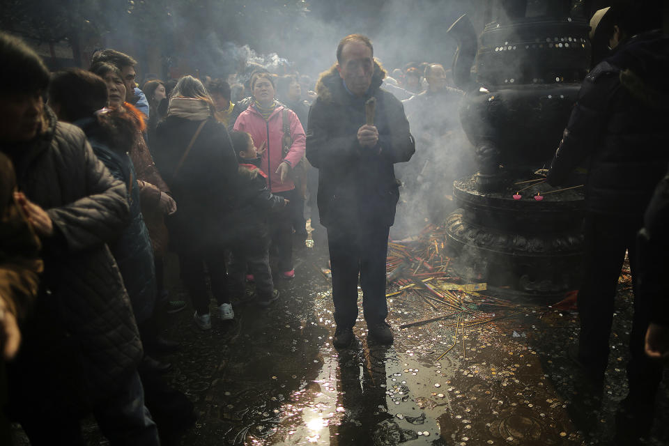 A man burns joss sticks while praying at Longhua Temple on the first day of the Lunar New Year in Shanghai, China on Sunday, Feb. 10, 2013.  Millions across China are celebrating the arrival of the Lunar New Year, the Year of the Snake, marked with a week-long Spring Festival holiday.   (AP Photo/Eugene Hoshiko)