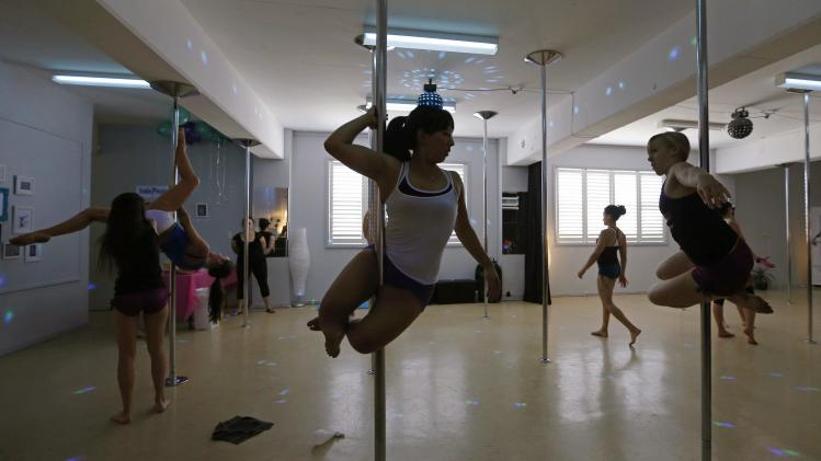Women practise their pole dancing moves during an International Women's Day event at a women's-only pole dancing fitness studio in Sydney