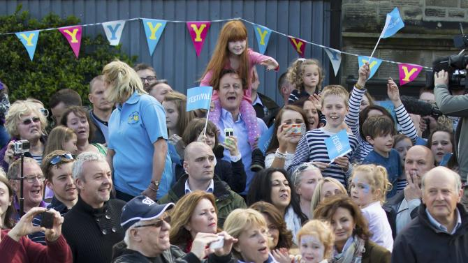 Britain's Prime Minister David Cameron holds Amelie Bone on his shoulders as he watches the Tour de Yorkshire cycle race pass through Addingham