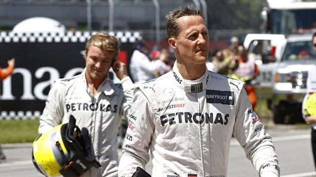 Mercedes Formula One driver Michael Schumacher (R) of Germany and team mate compatriot Nico Rosberg walk to the weighing platform following the qualifying session of the Canadian F1 Grand Prix