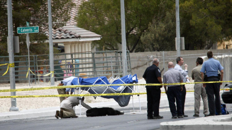 Metro officers and officials investigate the scene where an escaped male chimpanzee was shot and killed by a Metro officer, seen below the blue tent, on Ann Road just east of Jones Boulevard in North Las Vegas on Thursday, July 12, 2012. The chimpanzee, along with another female chimpanzee, escaped from a private residence near the scene. Metro police subdued and captured the female and shot and killed the male. (AP Photo/Las Vegas Review-Journal, Jessica Ebelhar) LOCAL TV OUT; LOCAL INTERNET OUT; LAS VEGAS SUN OUT