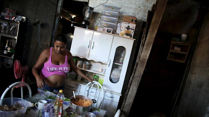 Kelly, who is seven months pregnant, looks at food next to the bathroom inside her stilt house, a lake dwelling also known as palafitte or 'Palafito', in Recife