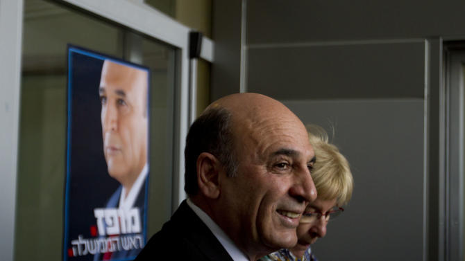 """Israeli Kadima Party candidate Shaul Mofaz smiles after casting his vote in a polling station in Kfar Saba, Israel,Tuesday, March 27, 2012. Israel's largest party, relegated to the opposition after 2009 national elections, is to choose its leader on Tuesday in a rematch between a former peace negotiator and a one-time defense chief who directed Israel's tough response to the last Palestinian uprising. The race between current Kadima Party chief Tzipi Livni and Shaul Mofaz is expected to be closely fought. Whoever wins will try to wrest power from Benjamin Netanyahu when Israelis next go to national elections, currently scheduled for October 2013. The poster reads """"Mofaz. Prime Minister.""""(AP Photo/Ariel Schalit)"""