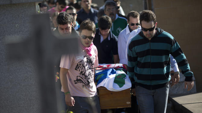 Relatives and friends carry the coffin of Vinicius Rosado through a cemetery during his burial in Santa Maria, Brazil, Monday, Jan. 28, 2013. A fast-moving fire roared through the crowded, windowless Kiss nightclub in this southern Brazilian city early Sunday, killing 233 people. Many of the victims were under 20 years old, including some minors. (AP Photo/Felipe Dana)