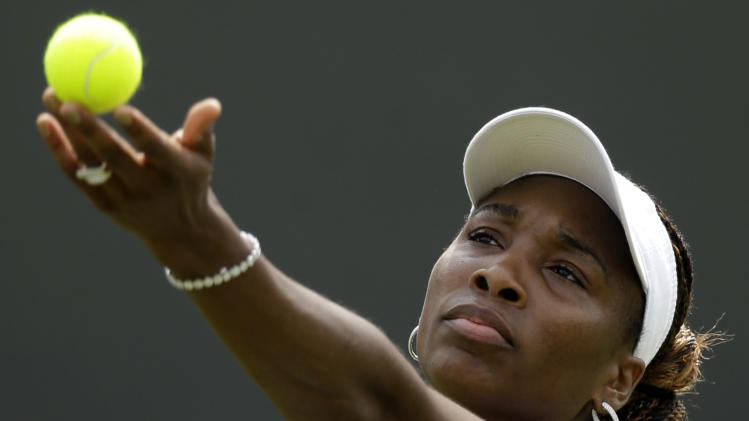 Venus Williams of the United States tosses the tennis ball to serve to Elena Vesnina of Russia during a first round women's singles match at the All England Lawn Tennis Championships at Wimbledon, England, Monday, June 25, 2012. (AP Photo/Alastair Grant)