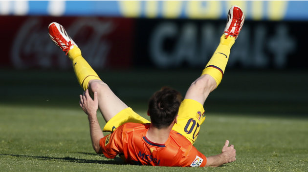 Barcelona's Lionel Messi falls during their Spanish First Division soccer match against Atletico Madrid at Vicente Calderon stadium in Madrid