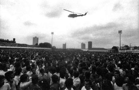 Members of the metalworkers union hold an assembly as a helicopter