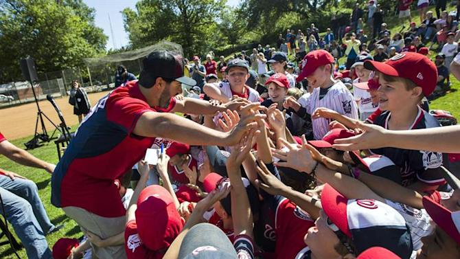 JL01. Washington (United States), 23/05/2015.- Washington Nationals starting pitcher Gio Gonzalez (L) greets young baseball players with the Northwest Washington Little League at Friendship Feld in Washington DC, USA, 23 May 2015. In March 2015, the Nationals donated baseball uniforms to little league teams across DC; Gonzalez and another Nationals player, Clint Robinson, came by the field to greet players and take photos. (Estados Unidos) EFE/EPA/JIM LO SCALZO
