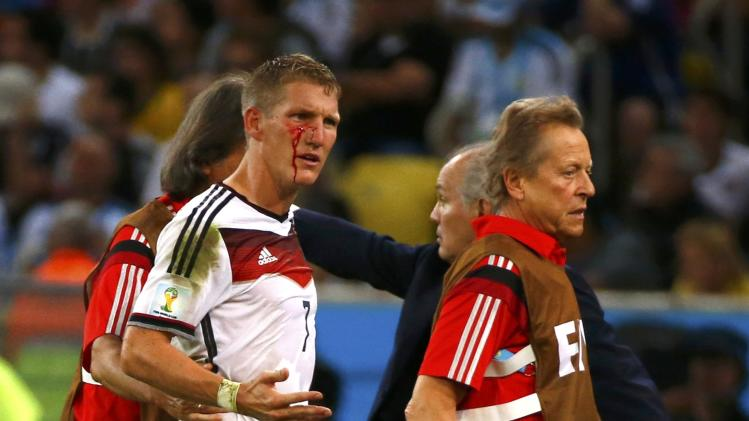 Germany's Bastian Schweinsteiger is led off the pitch while bleeding during extra time in the 2014 World Cup final between Germany and Argentina at the Maracana stadium