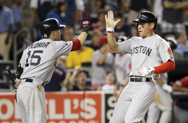 Boston Red Sox's Jacoby Ellsbury, right, is greeted by Dustin Pedroia after scoring the go-ahead run on a triple by Pedro Ciriaco during the ninth inning of the baseball game at Yankee Stadium in New York, Saturday, July 28, 2012. The Red Sox beat the New York Yankees 8-6. (AP Photo/Seth Wenig)