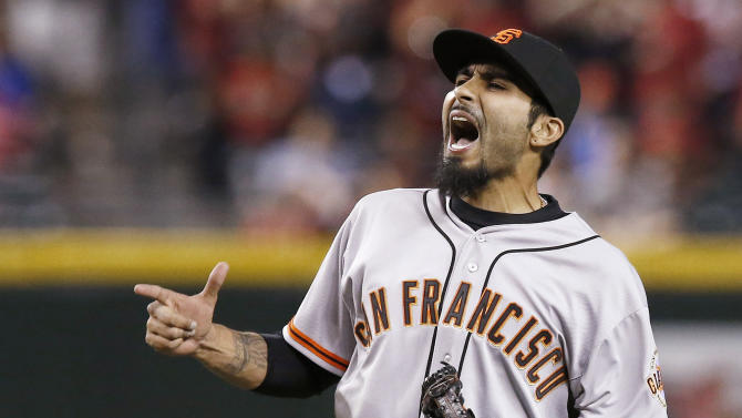 FILE - In a March 31, 2014, file photo San Francisco Giants' Sergio Romo celebrates the final out against the Arizona Diamondbacks during the ninth inning of an opening day baseball game  in Phoenix.  A person with knowledge of the negotiations says free agent reliever Sergio Romo is closing in on a new contract with the San Francisco Giants.   (AP Photo/Ross D. Franklin, file)